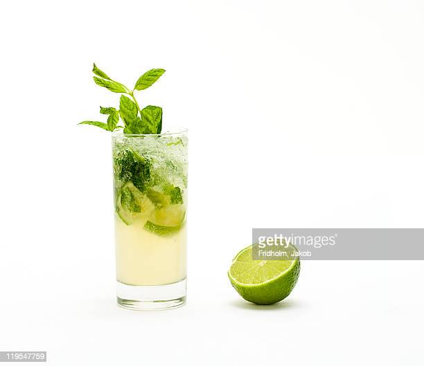 mojito with fresh mint leaves and lime on crushed ice - cocktail stock pictures, royalty-free photos & images
