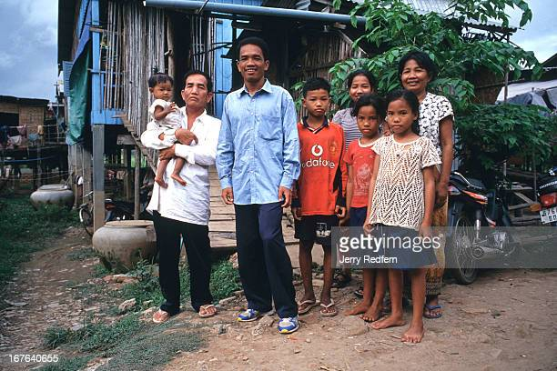 Mok Bonthoeun poses with his immediate family in front of the small house they share on the outskirts of Phnom Penh In a country where everyone is...