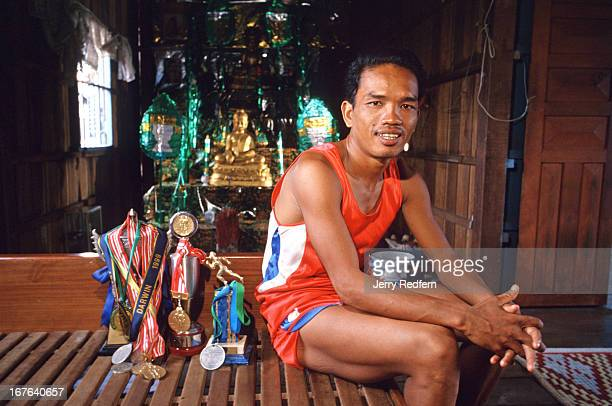 Mok Bunthoeun poses in his family home with many of the medals he has won in the past few years at races around the region The family Buddhist shrine...