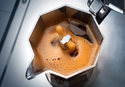 Moka with coffee on the stove top. Traditional italian coffee maker. 870507128
