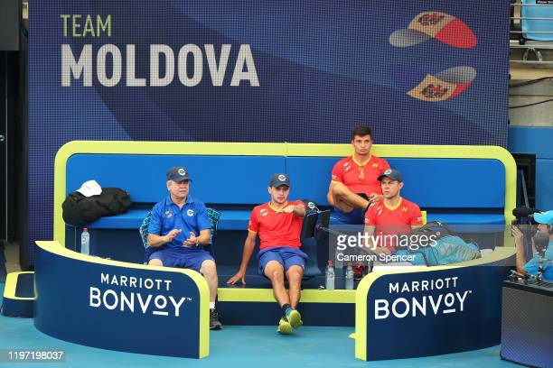 Moldova team captain Vladimir Albot and his team watch from their players box during the Group C singles match between Steve Darcis of Belgium and...