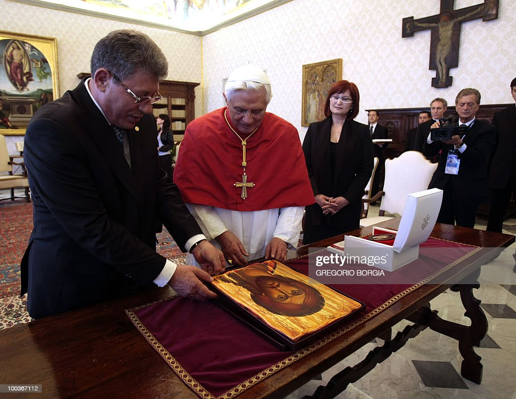 Moldovan interim President Mihai Ghimpu (L) offers a wooden icon of Jesus to Pope Benedict XVI (C) on May 24, 2010 during a private audience in the pontiff's private library at the Vatican.