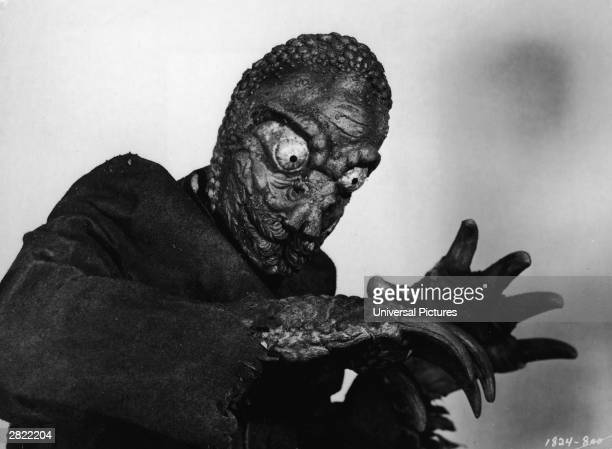 A mole person holds its arms out bent at the elbows in a film still from the horror movie 'The Mole People' directed by Virgil W Vogel 1956