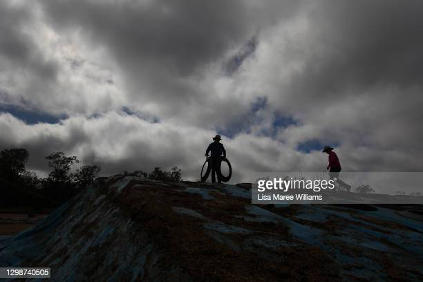 Molly and Karen Penfold prepare to pull back tarp covering silage for cattle feed at Mamaree on January 19, 2021 in Meandarra, Australia. COVID-19...