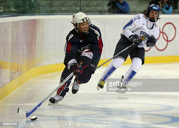 Molly Engstrom of the United States controls the puck in front of Saara Tuominen of Finland during the women's ice hockey bronze medal match during...
