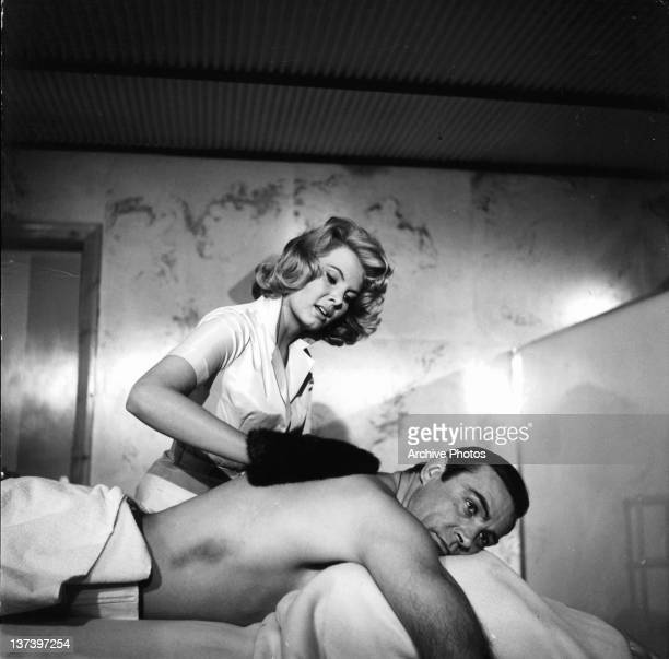 Molly Peters rubs Sean Connery back with a fur mitten in a scene from the film 'Thunderball', 1965.