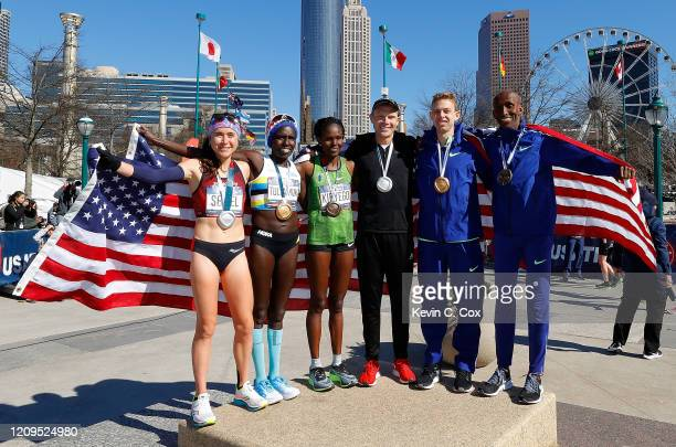 Molly Seidel, Aliphine Tuliamuk, Sally Kipyego, Jacob Riley, Galen Rupp, and Abdi Abdirahman pose together after finishing in the top three of the...