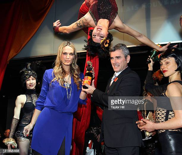 Molly Sims and Georges Duboeuf uncork the bottle at the 2010 Georges Duboeuf Beaujolais Nouveau celebration at District 36 on November 18 2010 in New...