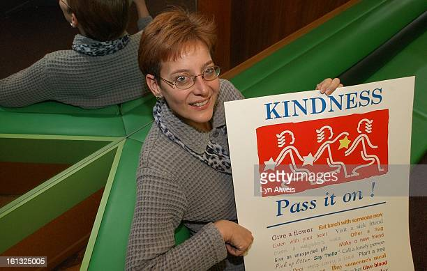 Molly Stuart JD is the President of The Random Acts of Kindness Foundation She poses with a poster