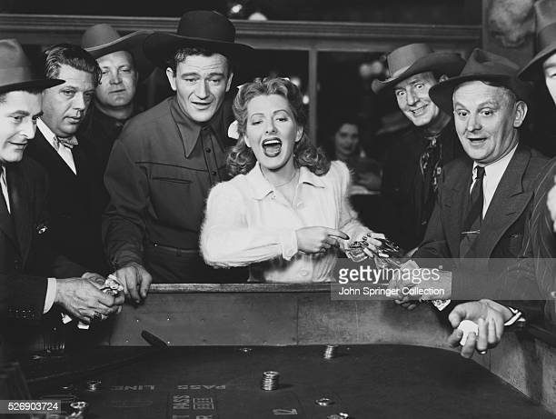 Molly Truesdale yells while tossing the dice at the craps table with Duke Hudkins and Waco second from the right in a scene from the 1943 film A Lady...