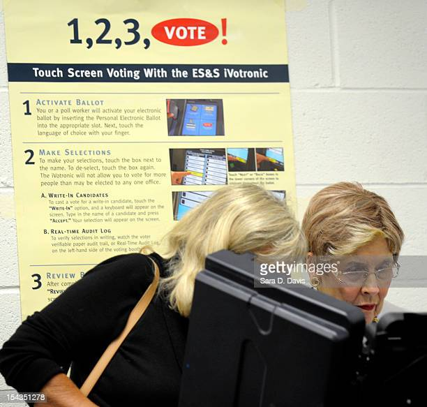 Molly Williford of Elm City North Carolina helps friend Pat Stewart of Wilson North Carolina cast her vote at the Board of Elections early voting...