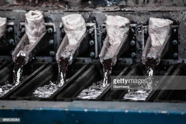 Molten aluminum pours from a molding machine into ingot molds at the Alumetal Group Hungary Kft aluminium processing plant in Komarom Hungary on...