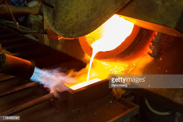 Molten gold pours from a crucible into a heated mould after refining at the Kaloti Jewellery LLC factory in Sharjah United Arab Emirates on Sunday...