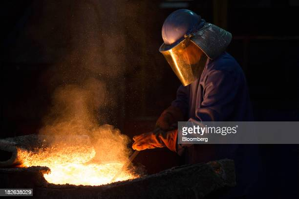 Molten iron is reflected in an employee's safety visor as he removes slag from the furnace at AGA Rangemaster Plc's foundry in Coalbrookdale UK on...