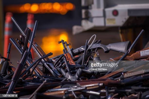 Molten slag is seen behind a pile of approximately 3500 confiscated guns about to be destroyed at the Gerdau Steel Mill understand supervision of the...