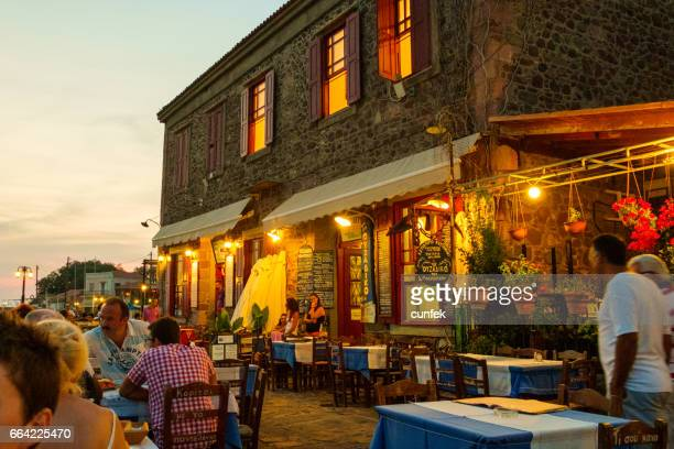 molyvos harbor restaurant by night - lesbos stock photos and pictures