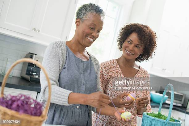 mom and adult daughter decorating eggs with string - happy easter mom ストックフォトと画像
