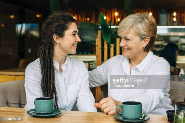 mom and adult daughter hug and laugh. - world sports championship stock pictures, royalty-free photos & images