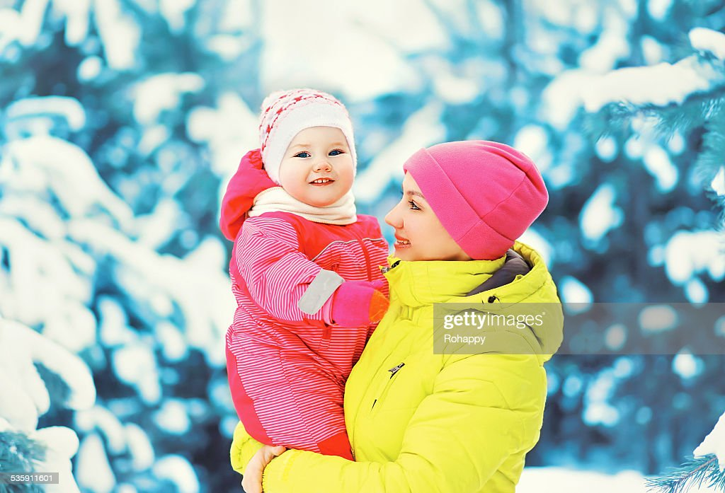 Mamá y bebé divertirse al aire libre en invierno día nival : Foto de stock