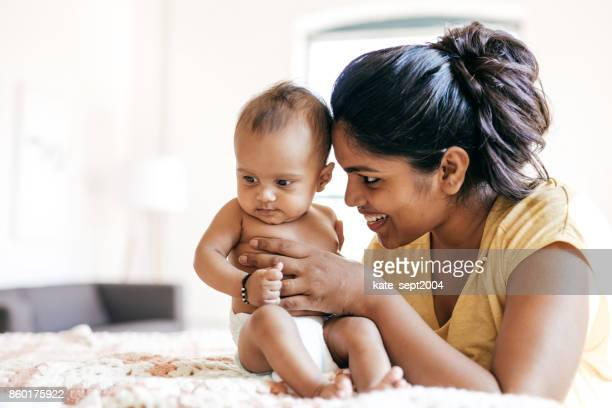 mom and baby indoor - indian woman stock photos and pictures
