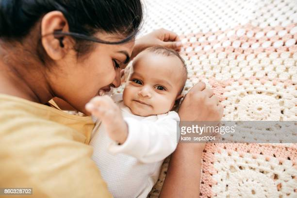 mom and baby indoor - indian baby stock photos and pictures