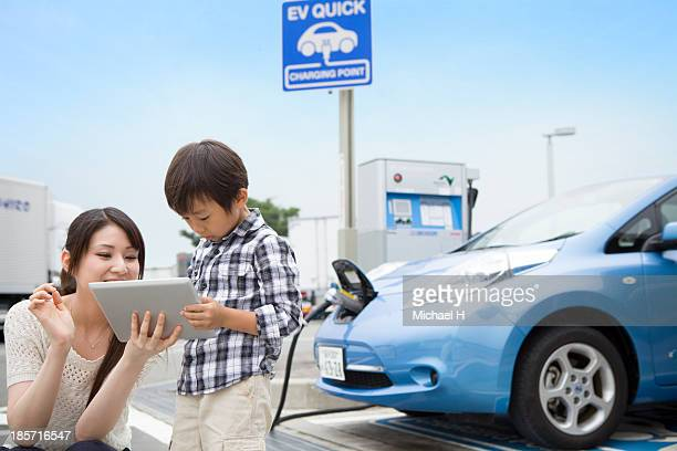 mom and child using tablet PC while charging car