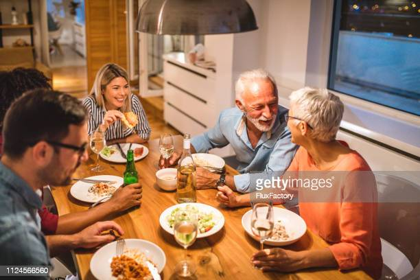 mom and dad enjoying dinner with their family - free thanksgiving stock pictures, royalty-free photos & images