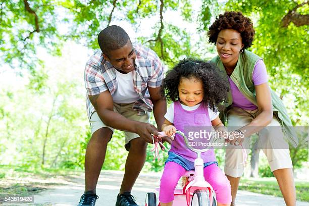 Mom and dad help toddler ride tricyle