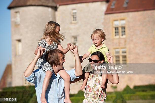 Mom and dad with kids on their shoulders