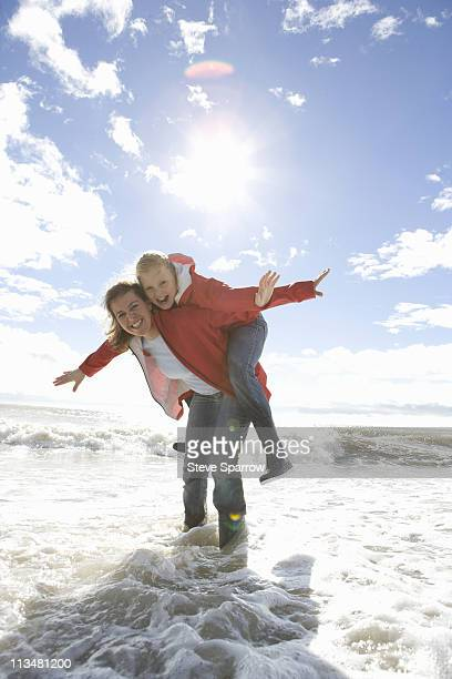Mom and daughter at beach piggyback ride
