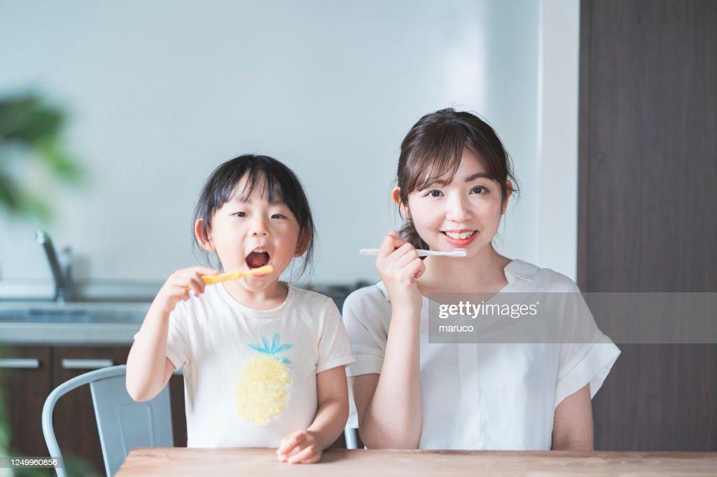 mom and daughter brushing teeth : Stock Photo