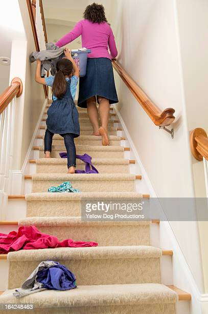 Mom and Daughter (6) carrying laundry up stairs