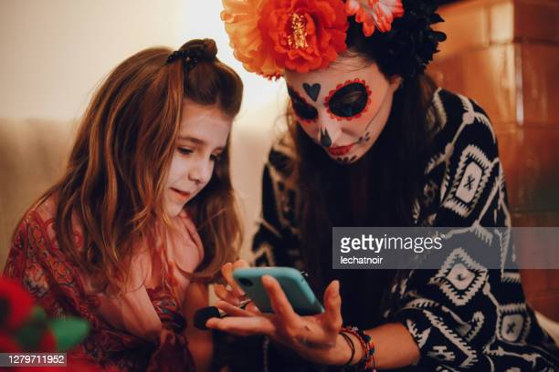 mom and daughter checking holiday greetings on the mobile phone - young goth girls stock pictures, royalty-free photos & images