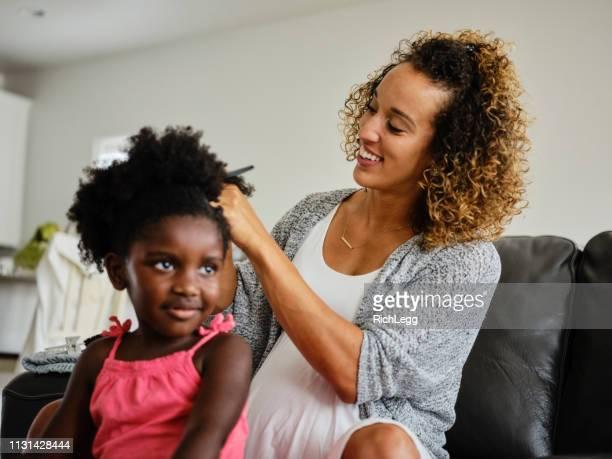 mamã e filha que fazem o cabelo - penteando - fotografias e filmes do acervo