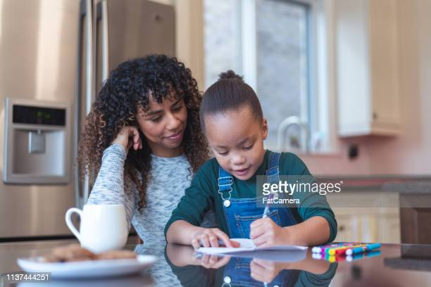 mom and daughter doing homework - workbook stock pictures, royalty-free photos & images