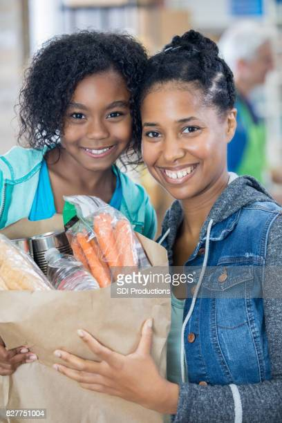 Mom and daughter donate bag of groceries at food bank