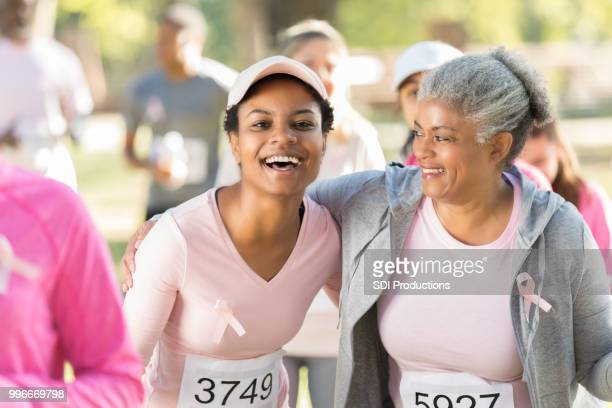 mom and daughter during breast cancer awareness walk - social awareness symbol stock photos and pictures