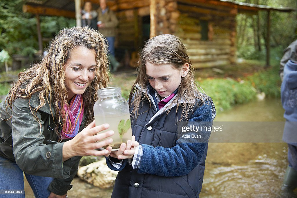 Mom and daughter examining insect in jar : Stock Photo