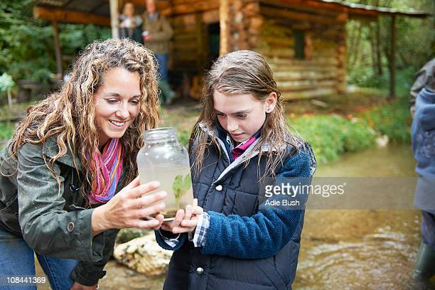 mom and daughter examining insect in jar - 40 44 jaar stock pictures, royalty-free photos & images