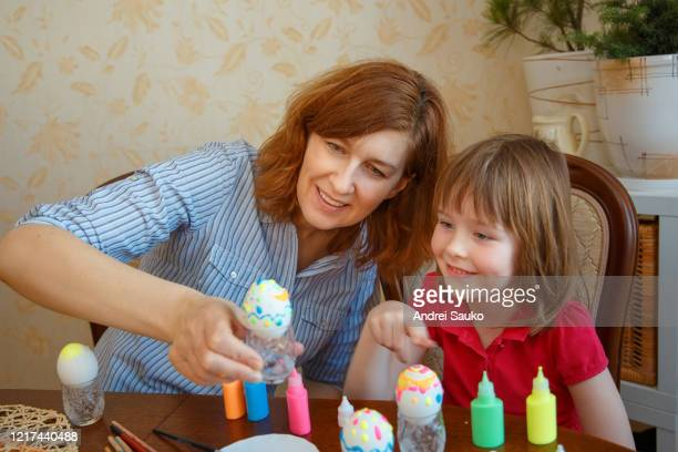 mom daughter have fun painting eggs