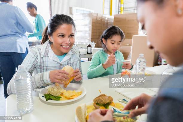 Mom and daughter have meal in soup kitchen