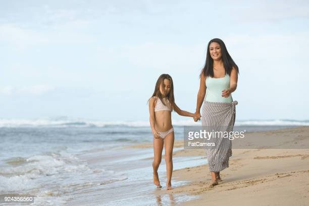 Mom and Daughter Holding Hands on a Beach Walk
