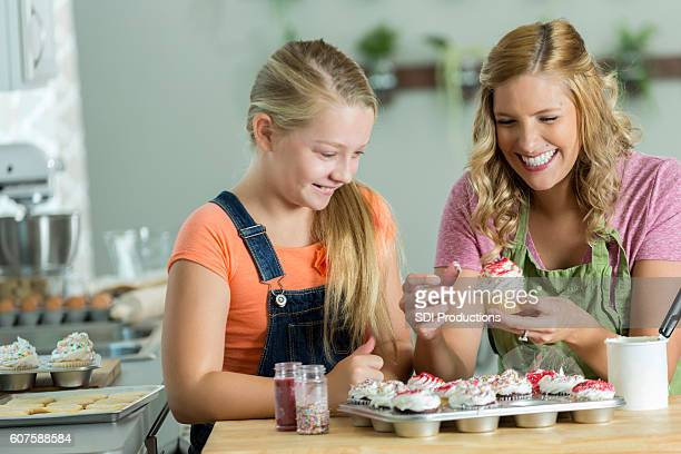 Mom and daughter laughing while they decorate cupcakes