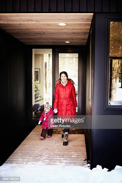 Mom (35-40) and daughter leaving the modern house