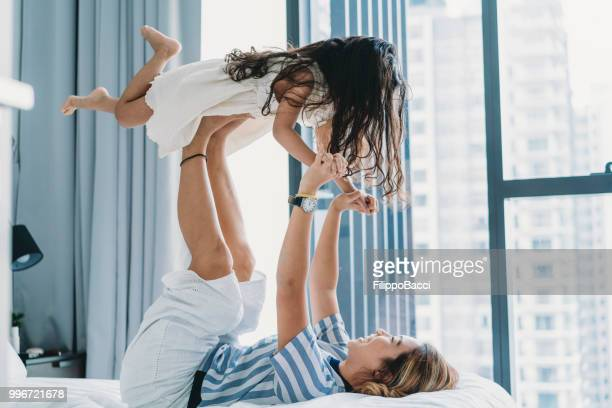mom and daughter playing together on the bed - chinese mothers day stock pictures, royalty-free photos & images