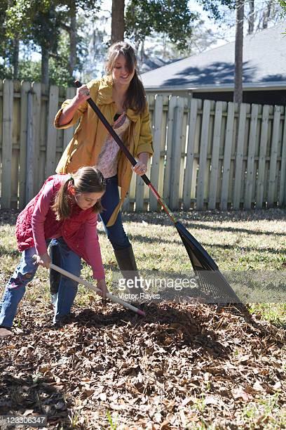 Mom and daughter raking leaves in yard