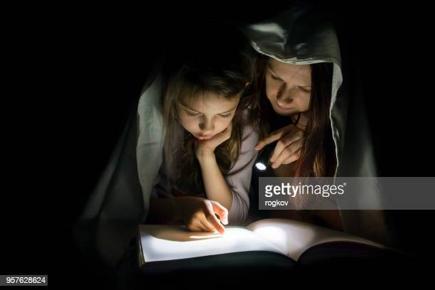 Mom and daughter read fairy tales in the dark under a blanket covering the book with a flashlight.