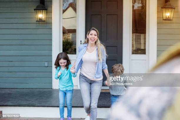 mom and daughter run to greet soldier - military spouse stock pictures, royalty-free photos & images