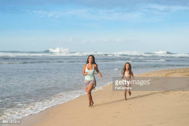 Mom and daughter running on the beach