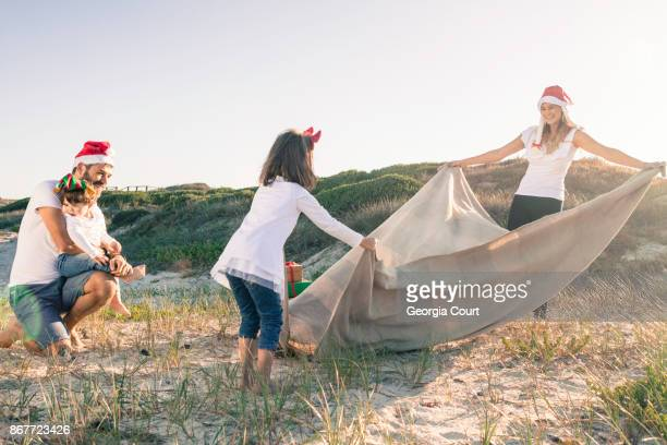 Mom and daughter spread out blanket family Christmas on the beach